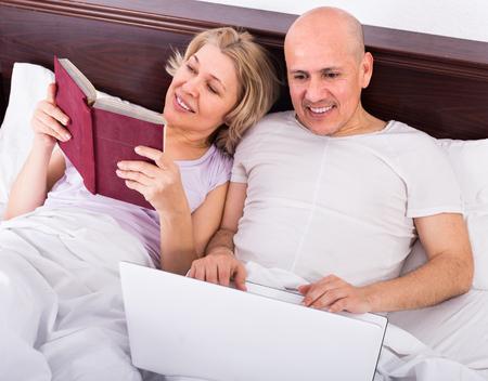 evening class: Mature couple burring with laptop indoors Stock Photo