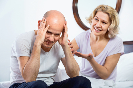 miserable: Positive smiling mature girl supporting frustraited boyfriend in difficuilt moment