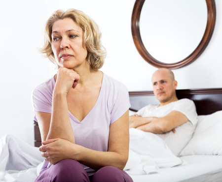 impotent: Mature man and sad woman getting through scandals and blamings in bedroom