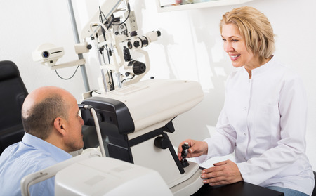 slit: Mature specialist examinating eyesight with aid of slit lamp