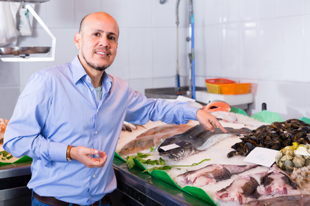 male customer buying fish and chilled seafood in shop Stock Photo