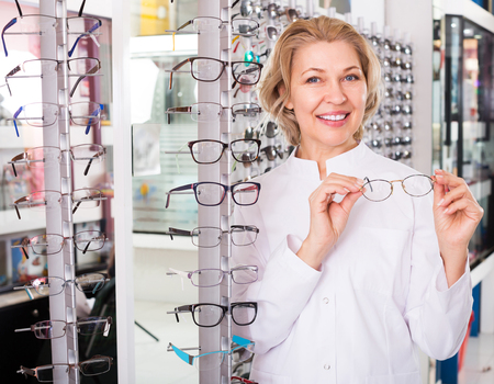 45 50: Mature female optician standing near display with spectacles and smiling Stock Photo
