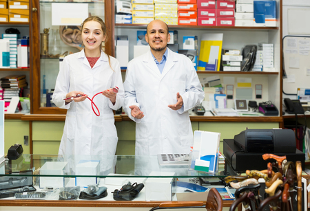 orthopaedic: Two positive spanish orthopedists working in special store with orthopaedic goods