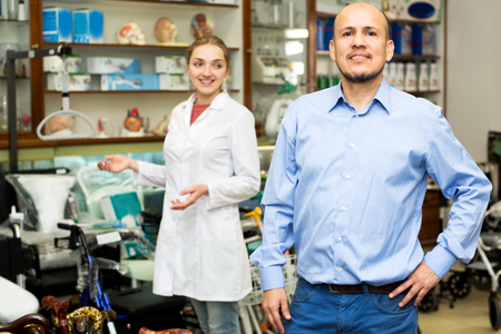 orthopaedic: Female consultant offering wheelchair to mature customer in orthopaedic store Stock Photo