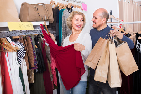 50s: Elderly spouses 50s buying new dress and smiling in boutique