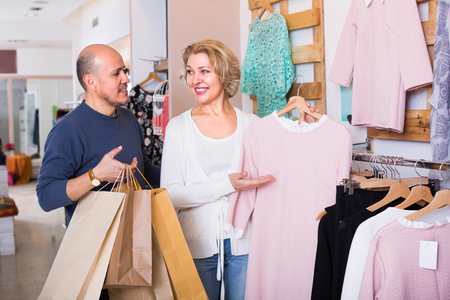 55 60: Happy mature couple choosing new dress for wife in boutique and smiling
