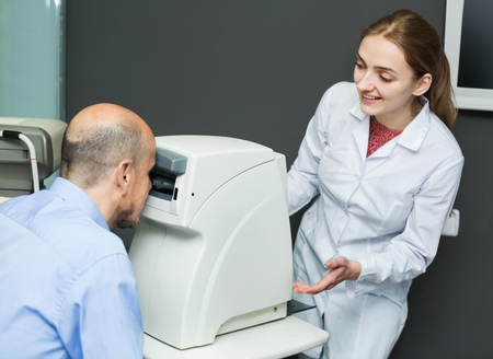 slit: Young female optician doing eye examination with aid of slit lamp