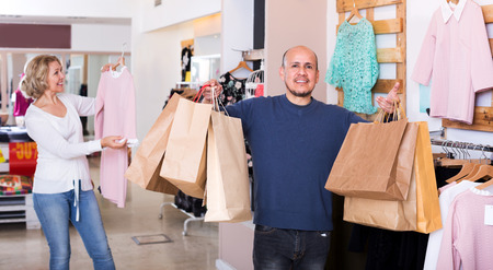 55 60: Man with bags waiting for woman selecting dress in boutique