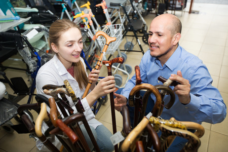 shopgirl: Positive orthopedist consulting elderly client about walking sticks in shop