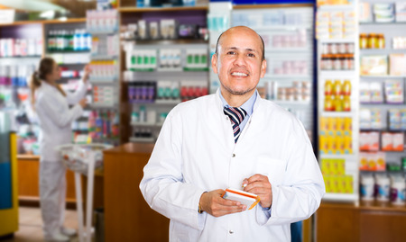 farmacy: Elderly pharmacist and female assistant working at farmacy reception