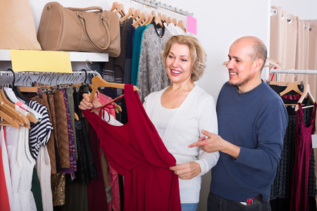 55 60: Elderly spouses buying new dress and smiling in boutique
