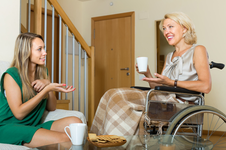 incapacitated: Handicapped smiling woman talking with female guest at the table. Focus on young