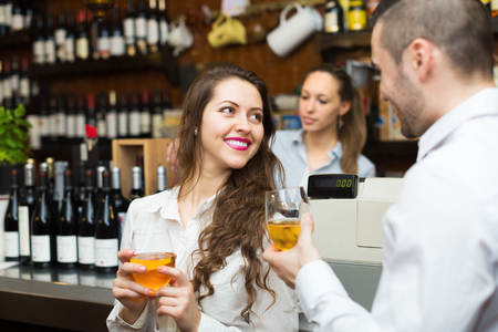 woman drinking wine: Happy restaurant visitors waiting for table and drinking wine at bar