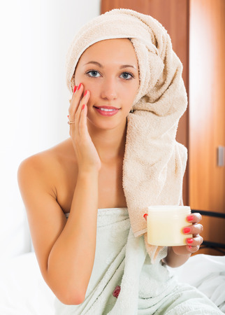 caring for: Blonde woman caring for skin with cosmetic cream in bed at home