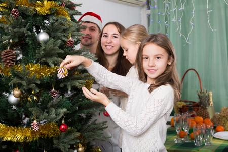 christmas tree decoration: Young parents with two little daughters decorating Christmas tree and smiling. Focus on girl Stock Photo