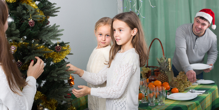 decorating christmas tree: Young parents with two cute little daughters decorating Christmas tree and serving table at home. Focus on girl