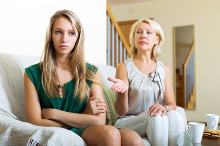 fracas: Sad woman and her mature mother having conflict on sofa