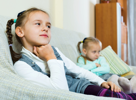miserable: Portrait of two small upset miserable girls having conflict at home