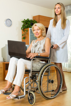 incapacitated: Female social worker and disabled mature woman on chair with laptop. Focus on woman