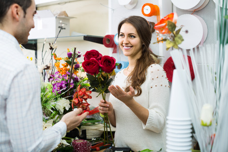 flower seller: Woman seller helping to pick floral bouquet of flowers client at flower shop