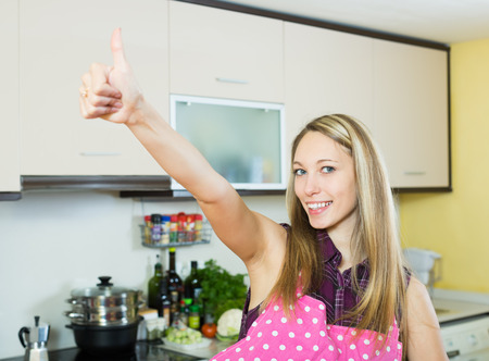 staying: Pretty blonde girl staying in kitchen and showing thumbs up