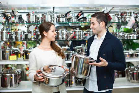 utensilios de cocina: Joven pareja sonriente feliz en la secci�n de utensilios de cocina en el hipermercado Foto de archivo