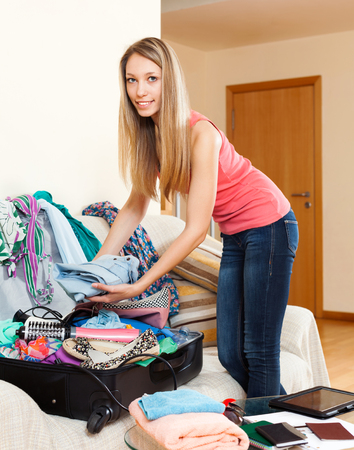 novelties: young woman standing in a room and putting things in an open suitcase Stock Photo