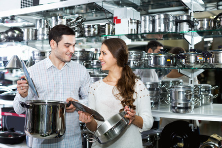 utensilios de cocina: Young positive smiling couple in the cookware section at hypermarket
