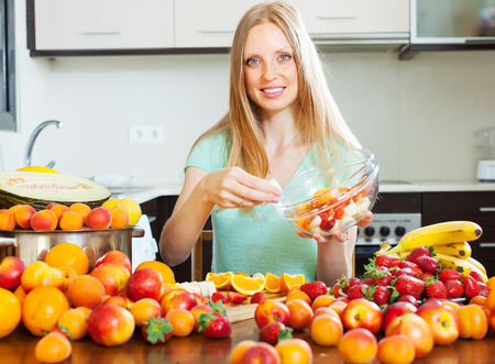 30 to 35: long-haired blonde girl cooking fruit salad with fruits