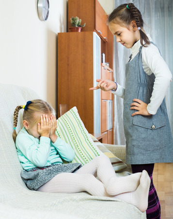 Serious european girl lecturing little sister in domestic interior