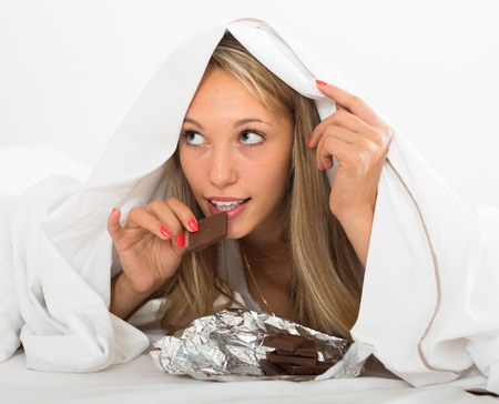 furtively: Young blonde woman eating chocolate in bed