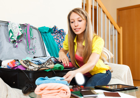 novelties: Young woman is packing a suitcase sitting on the couch in the room