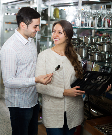 flatware: woman and man chooses flatware in the cookware section at shop