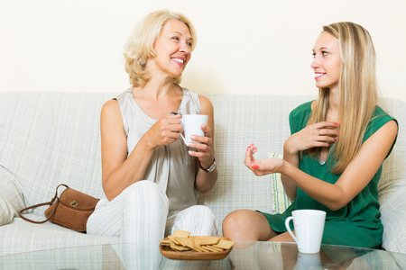 20 30 years: Happy smiling aged mother with adult daughter in home interior. Focus on mature Stock Photo