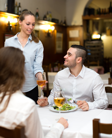 ordered: Spouses eating out in a rural restaurant while young waitress is bringing them the food that they had ordered