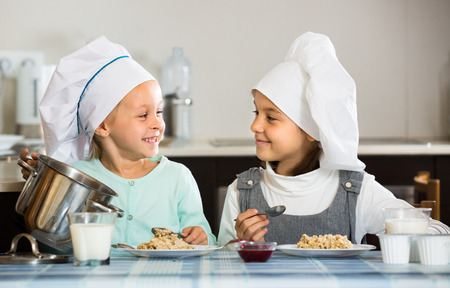 kasha: Two little girls having breakfast with kasha indoors