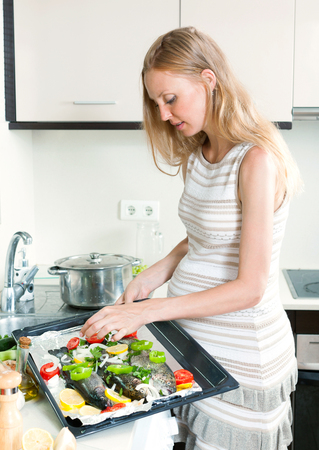 pregnant blonde: Pregnant blonde young woman cooking trout fish in pan at kitchen