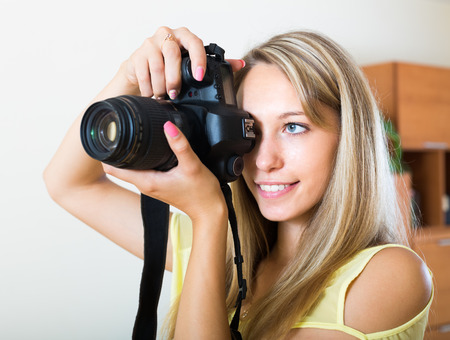 photocamera: Young smiling girl working with professional photocamera at home Stock Photo