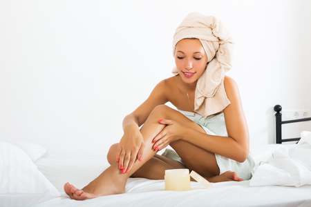 foot cream: Smiling blonde woman using cosmetic cream in bed