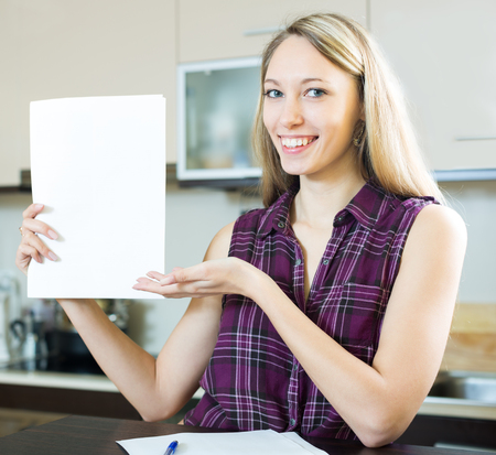 utility payments: Cheerful long-haired woman reading documents in the kitchen Stock Photo