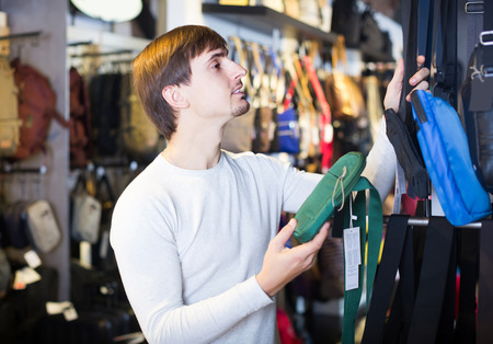25 35: Handsome russian male customer purchasing new satchel in store