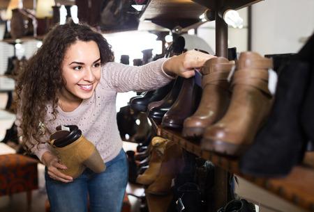 buying shoes: adulto americano zapatos de invierno femenina de compra en la tienda de zapatos femeninos Foto de archivo