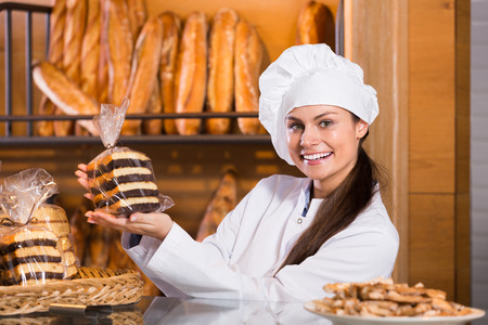 shopgirl: Happy shopgirl posing in bakery with bread and different pastry