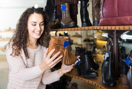 comprando zapatos: young american female buying winter female shoes in  shoe store