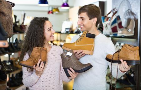 comprando zapatos: Pares alegres que la compra de zapatos de invierno en una tienda de zapatos Foto de archivo