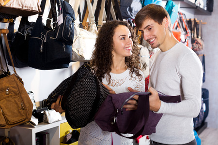shopgirl: Happy female shopgirl helping adult man to select handbag in store Stock Photo