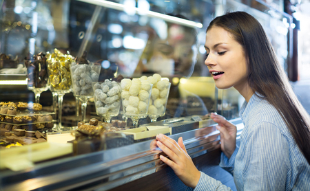 25 35: positive spanish brunette girl buying dark and white chocolate with fillings