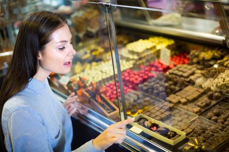 praline: Excited brunette girl choosing delicious ganaches, praline and chocolates