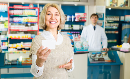 50 to 60: Smiling mature female patient buying medicine in pharmacy