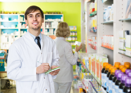 farmacy: Portrait of smiling russian male pharmacists working in modern farmacy
